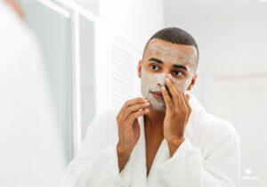 homem se olhando no espelho enquanto aplica produto de beleza no rosto